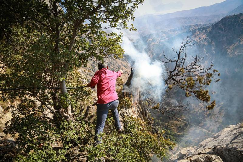 A volunteer works to extinguish a fire  Jird Harar, in Lebanon's Akkar region on Aug. 30, 2020.