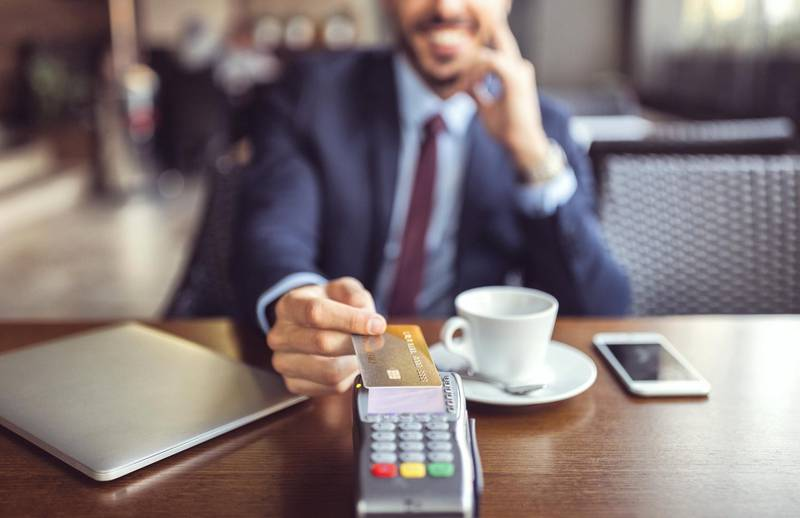 Smiling man at coffee break paying with credit card