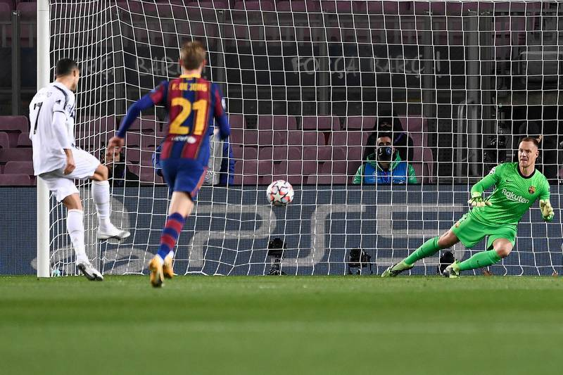 Juventus' Portuguese forward Cristiano Ronaldo (L) scores a penalty during the UEFA Champions League group G football match between Barcelona and Juventus at the Camp Nou stadium in Barcelona on December 8, 2020. (Photo by Josep LAGO / AFP)