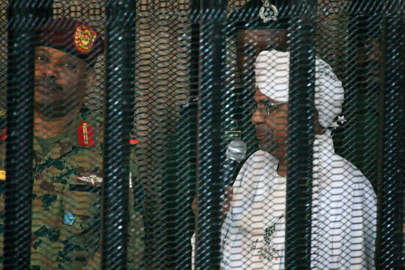 (FILES) In this file photo taken on August 19, 2019, Sudan's deposed military ruler Omar al-Bashir stands in a defendant's cage during the opening of his corruption trial in Khartoum. The Arab Spring uprisings are nearly a decade-old and moribund but protests in Sudan and three other new countries last year revealed that the spirit of the revolts that lit up 2011 is still alive. The countries swept up by the latest revolts had initially stood on the sidelines as a contagion of uprisings gripped countries in the Middle East and North Africa in 2011. But in 2019 they led calls for an end to the same regional economic precariousness, corruption, and unresponsive governance that fuelled the Arab protests years earlier. / AFP / Ebrahim HAMID