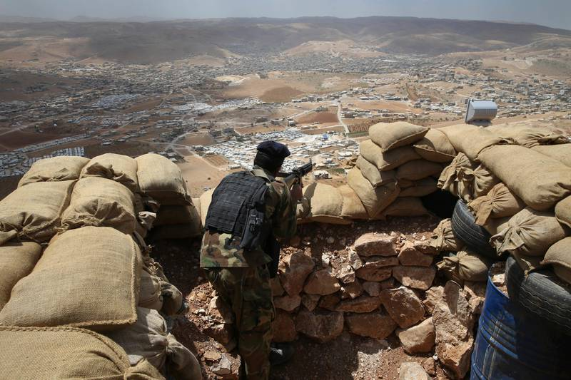 FILE -- In this June 19, 2016 file photo, a Lebanese army soldier takes his position overlooking an area controlled by the Islamic State group at the edge of the town of Arsal, in northeast Lebanon. Lebanon's U.S.-backed military is gearing up for a long awaited assault to dislodge hundreds of IS militants from a remote corner of northeastern Lebanon near the border with Syria, seeking to end a years-long threat posed to neighboring towns and villages by the extremists. (AP Photo/Hussein Malla, File)
