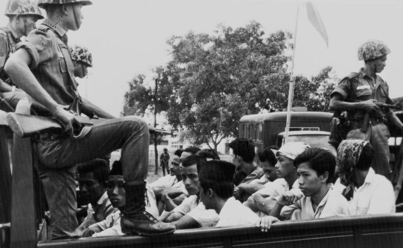 FILE - In this Oct. 30, 1965, file photo, members of the Youth Wing of the Indonesian Communist Party (Pemuda Rakjat) are watched by soldiers as they are taken to prison in Jakarta following a crackdown on communists after an abortive coup against President Sukarno's government earlier in the month. Declassified files have revealed new details of American government knowledge and support of an Indonesian army extermination campaign that killed several hundred thousand civilians during anti-communist hysteria in the mid-1960s. (AP Photo/File)