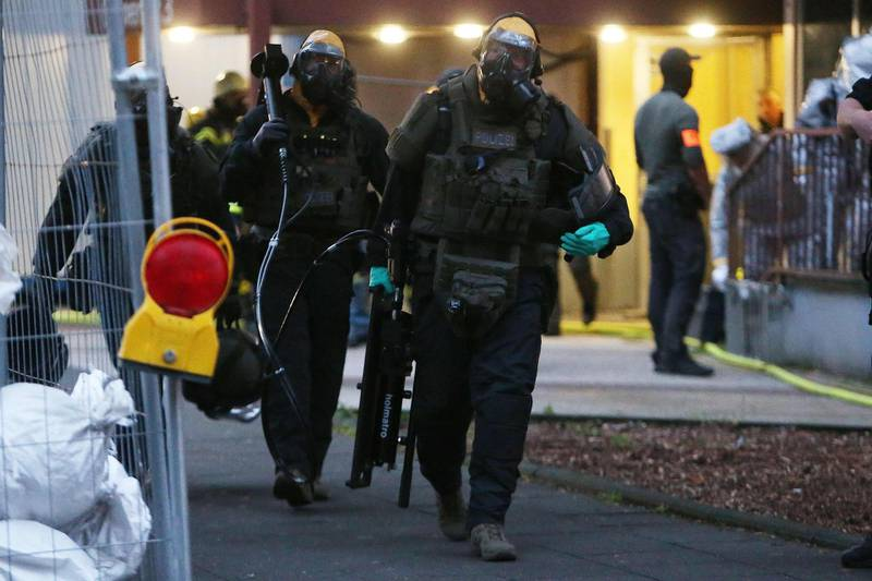 """Police officers, including special forces wearing protective suits walk out of a building on late June 12, 2018 in Cologne, where German police have arrested a Tunisian man after discovering """"toxic substances"""" at his flat.   The man and his wife, whose nationality was not released, were detained late June 12, 2018 after officers raided their flat and came across """"unknown substances"""" that are now being analysed by specialists, Cologne police said in a statement. - Germany OUT  / AFP / dpa / David Young"""