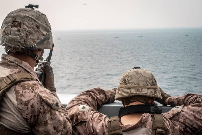 Marines onboard the amphibious transport dock ship USS John P. Murtha (LPD 26) watch nearby Iranian fast inland attack craft, as it transits the Strait of Hormuz, off Oman, in this undated handout picture released by U.S. Navy on August 12, 2019. Adam Dublinske/U.S. Navy/Handout via REUTERS ATTENTION EDITORS- THIS IMAGE HAS BEEN SUPPLIED BY A THIRD PARTY.