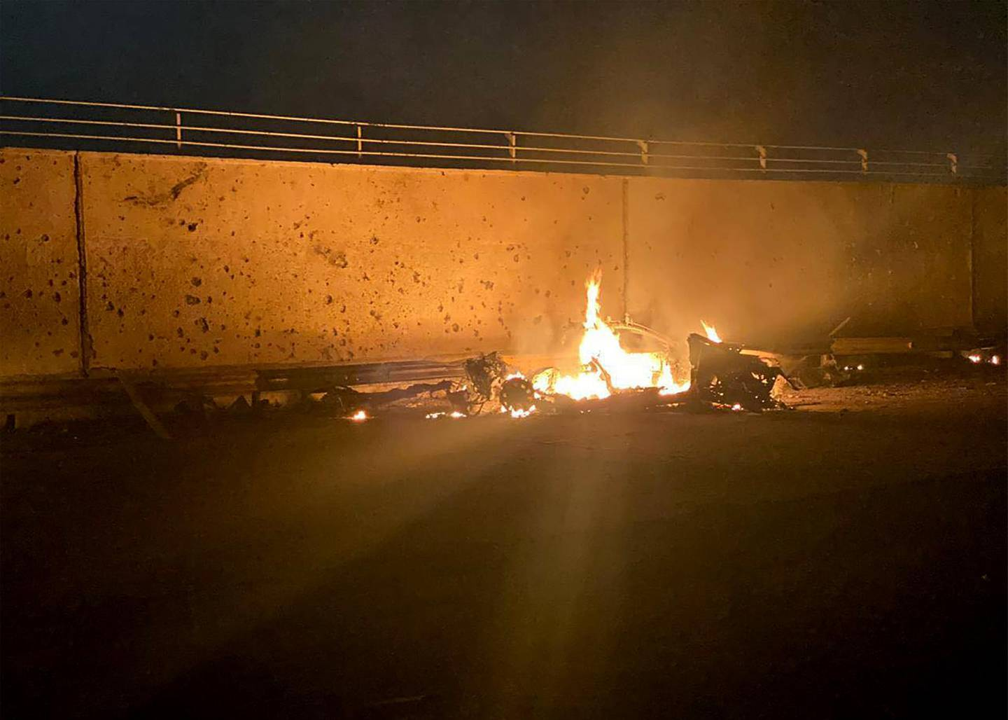 """TOPSHOT - A picture published by the media office of the Iraqi military's joint operations forces on their official Facebook page shows a destroyed vehicle on fire following a US strike on January 3, 2020 on Baghdad international airport road in which top Iranian commander Qasem Soleimani was killed along with eight others, including the deputy head of Iraq's powerful Hashed al-Shaabi paramilitary force. Early Friday, a volley of US missiles hit Baghdad's international airport, striking a convoy belonging to the Hashed al-Shaabi, an Iraqi paramilitary force with close ties to Iran. Soleimani was killed in the US strike on the Iraqi capital's airport, according to Hashed, in a dramatic escalation of tensions between Washington and Tehran. - === RESTRICTED TO EDITORIAL USE - MANDATORY CREDIT """"AFP PHOTO / HO / IRAQI MILITARY"""" - NO MARKETING NO ADVERTISING CAMPAIGNS - DISTRIBUTED AS A SERVICE TO CLIENTS ===  / AFP / IRAQI MILITARY / - / === RESTRICTED TO EDITORIAL USE - MANDATORY CREDIT """"AFP PHOTO / HO / IRAQI MILITARY"""" - NO MARKETING NO ADVERTISING CAMPAIGNS - DISTRIBUTED AS A SERVICE TO CLIENTS ==="""
