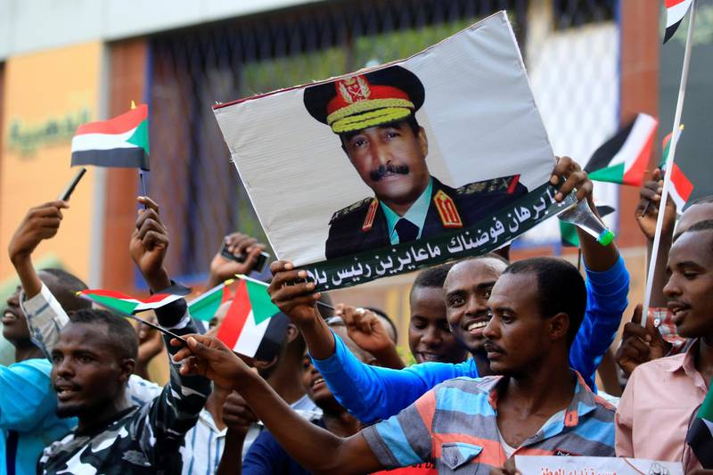 """Sudanese supporters of the ruling Transitional Military Council (TMC) hold up a sign showing a portrait of its head General Abdel Fattah al-Burhan with a caption below reading in Arabic """"we have delegated you Burhan, we want no president but you"""", during a rally in the centre of the capital Khartoum on May 31, 2019. (Photo by ASHRAF SHAZLY / AFP)"""