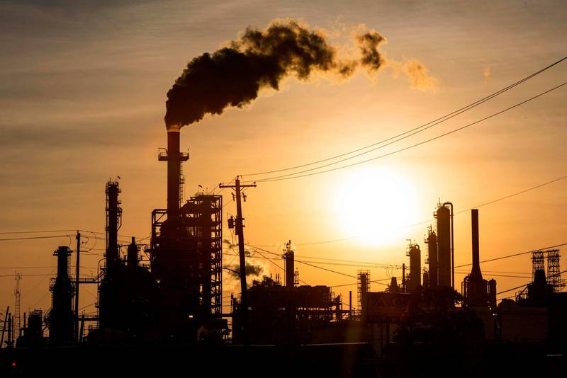 TOPSHOT - The sun sets behind smoke rising from the LyondellBasell-Houston Refining plant in Houston, Texas, on April 20, 2020. US oil prices crashed to unprecedented lows on April 20 as futures in New York ended in negative territory for the first time amid a devastating supply glut that has forced traders to pay others to take the crude off their hands. / AFP / AFP  / Mark Felix
