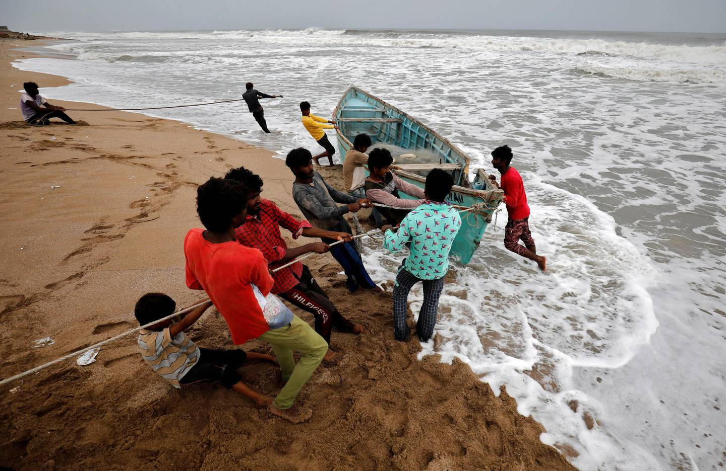People move a fishing boat to a safer place along the shore ahead of Cyclone Tauktae in Veraval in the western state of Gujarat, India, May 17, 2021. REUTERS/Amit Dave