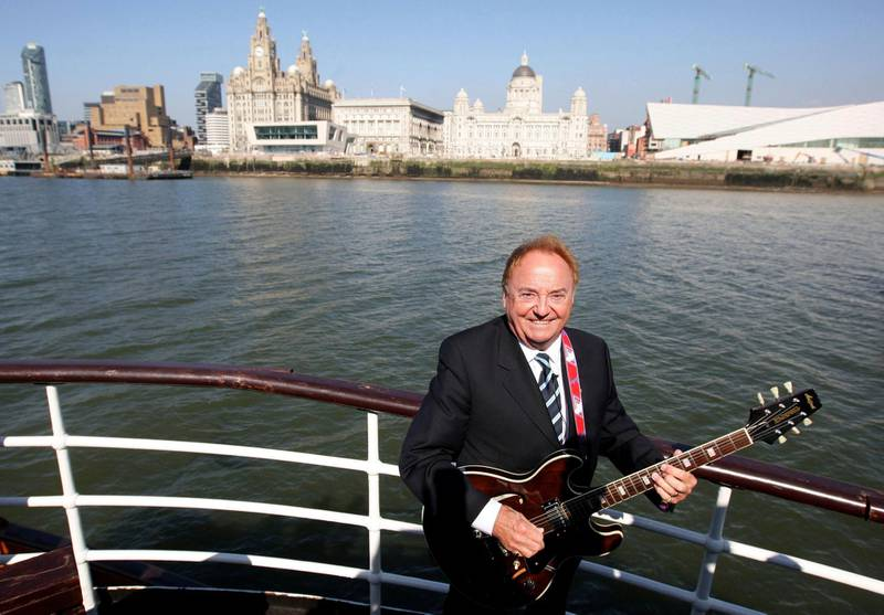 """FILE - This April 20, 2009 file photo shows Gerry Marsden on board the Mersey ferry. Gerry Marsden, the British singer and lead singer of Gerry and the Pacemakers, who was instrumental in turning a song from the Rodgers and Hammerstein musical """"Carousel"""" into one of the great anthems in the world of football, has died. He was 78. (Dave Thompson/PA via AP, File)"""