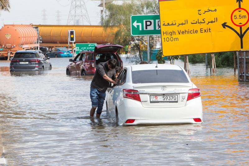 Dubai, United Arab Emirates - A car owner helped by some friends helplessly pushing his car out of the flooded street closed to Batuta and Discover Gardens streets.  Ruel Pableo for The National