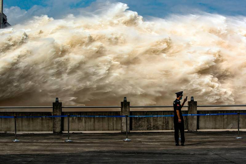 This photo taken on July 19, 2020 shows a security guard looking at his smartphone while water is released from the Three Gorges Dam, a gigantic hydropower project on the Yangtze river, to relieve flood pressure in Yichang, central China's Hubei province. Rising waters across central and eastern China have left over 140 people dead or missing, and floods have affected almost 24 million since the start of July, according to the ministry of emergency management. - China OUT  / AFP / STR