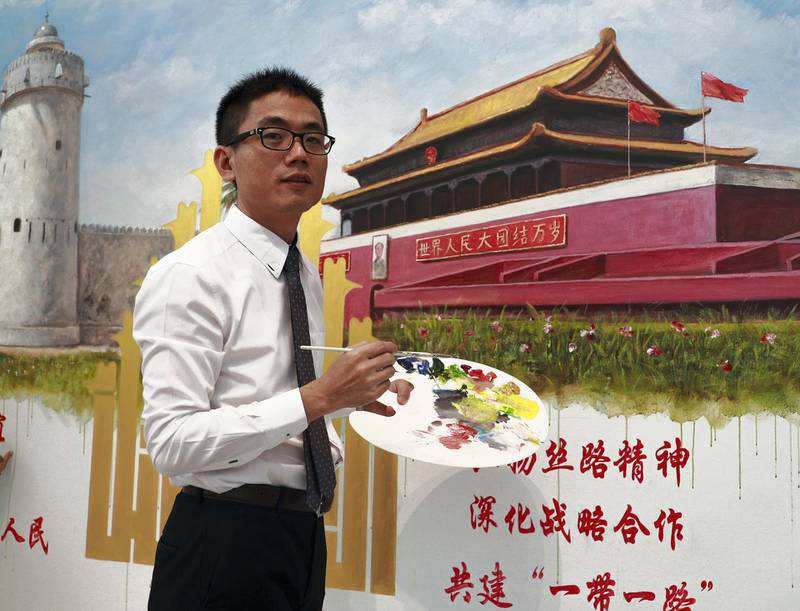 Abu Dhabi, U.A.E., July 17, 2018.   The Launch of China Week at Manarat Al Saadiyat with guests of honor, Noura Al Kaabi, Minister of Culture and Knowledge Development and Ni Jian, Ambassador of China.--  Chinese artist and teacher, Jack Lee infront of his collaborative painting with Emirati Artist, Mohammed Mandi of the Tiananmen Square entrance and the Qasr Al hosn Fort.  Victor Besa / The NationalSection:  NAReporter:  John Dennehy