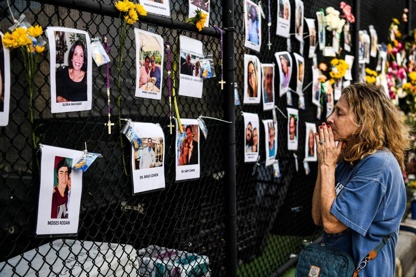 TOPSHOT - A woman prays in front of photos at the makeshift memorial for the victims of the building collapse, near the site of the accident in Surfside, Florida, north of Miami Beach on June 27, 2021. The death toll after the collapse of a Florida apartment tower has risen to nine, officials said Sunday, with more than 150 people still missing and their weary families waiting more than three days afterwards for information as to their fate. The outlook grew more and more grim by the hour, however, as the slow rescue operation, involving workers sorting nonstop through the rubble in torrid heat and high humidity, carried on.  / AFP / CHANDAN KHANNA