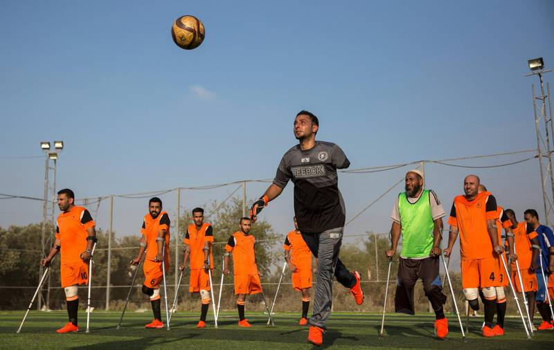 Palestinian goal keeper Islam Amoun (center) and other players during a practice session for Gaza's first amputee football team held at the municipal ball field of Deir Al Balah ,Gaza on July 16,2018. Islam was critically injured and lost his left arm by an Israeli air strike nearby his home during the war in 2014. (Photo by Heidi Levine for The National).
