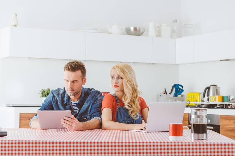 Adult couple after argument, sitting at the table in the kitchen at home. Man using a digital tabet and woman typing on laptop, peeking at her partner.
