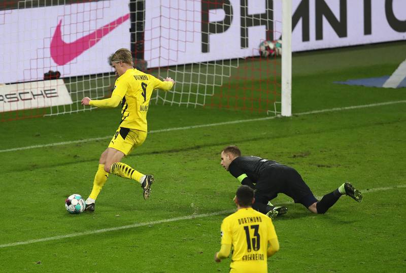 LEIPZIG, GERMANY - JANUARY 09: Erling Haaland of Borussia Dortmund scores their team's third goal past Peter Gulacsi of RB Leipzig during the Bundesliga match between RB Leipzig and Borussia Dortmund at Red Bull Arena on January 09, 2021 in Leipzig, Germany. Sporting stadiums around Germany remain under strict restrictions due to the Coronavirus Pandemic as Government social distancing laws prohibit fans inside venues resulting in games being played behind closed doors. (Photo by Maja Hitij/Getty Images)