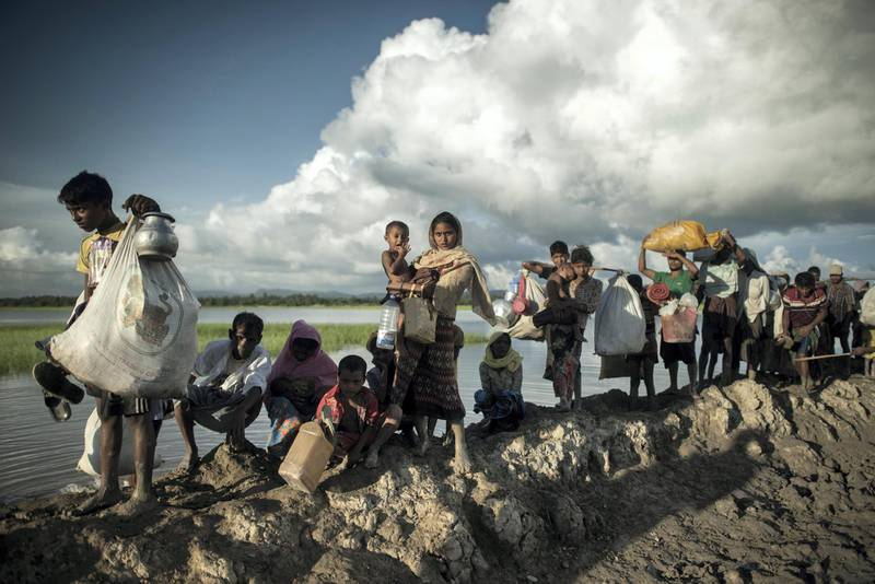 Rohingya refugees walk after crossing the Naf river from Myanmar into Bangladesh in Whaikhyang on October 9, 2017.  A top UN official said on October 7 Bangladesh's plan to build the world's biggest refugee camp for 800,000-plus Rohingya Muslims was dangerous because overcrowding could heighten the risks of deadly diseases spreading quickly. The arrival of more than half a million Rohingya refugees who have fled an army crackdown in Myanmar's troubled Rakhine state since August 25 has put an immense strain on already packed camps in Bangladesh.  / AFP PHOTO / FRED DUFOUR