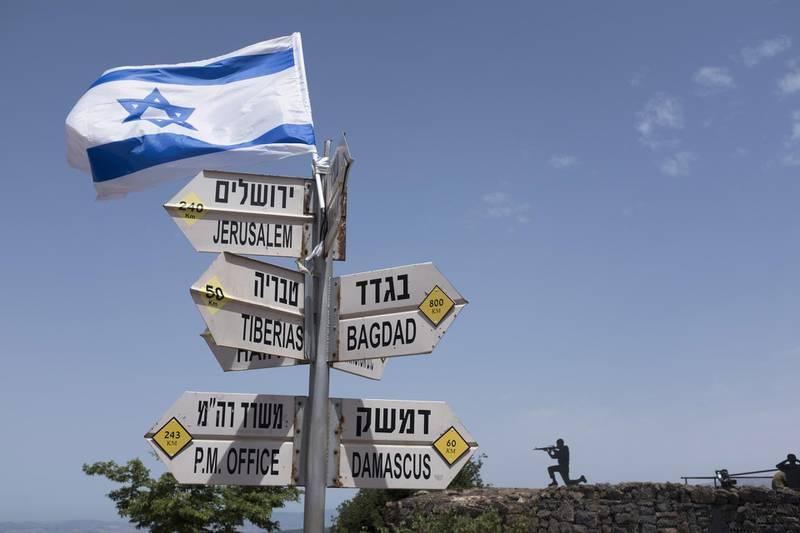 GOLAN HEIGHTS - MAY 10:  (ISRAEL OUT)  A silhouette sculpture of an Israeli soldier standing guard is seen next  to a signs pointing out distance to different cities on Mount Bental next to the Syrian border on May 10, 2018 in the Israeli-annexed Golan Heights. Some 20 rockets were fired at Israeli military bases by Iranian forces from southern Syria just after midnight on Thursday, sparking the largest ever direct clash between Jerusalem and Tehran, with Israeli jets targeting numerous Iranian-controlled sites across Syria. On Monday  U.S. President Donald Trump pulls out of the Iran deal.  (Photo by Lior Mizrahi/Getty Images) *** BESTPIX ***