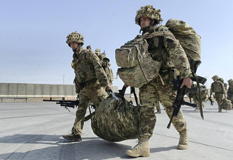 British soldiers walk with their gear after arriving in Kandahar on October 27, 2014, as British and US forces withdraw from the Camp Bastion-Leatherneck complex in Helmand province. British forces October 26 handed over formal control of their last base in Afghanistan to Afghan forces, ending combat operations in the country after 13 years which cost hundreds of lives. The Union Jack was lowered at Camp Bastion in the southern province of Helmand, while the Stars and Stripes came down at the adjacent Camp Leatherneck -- the last US Marine base in the country. AFP PHOTO/WAKIL KOHSAR (Photo by WAKIL KOHSAR / AFP)