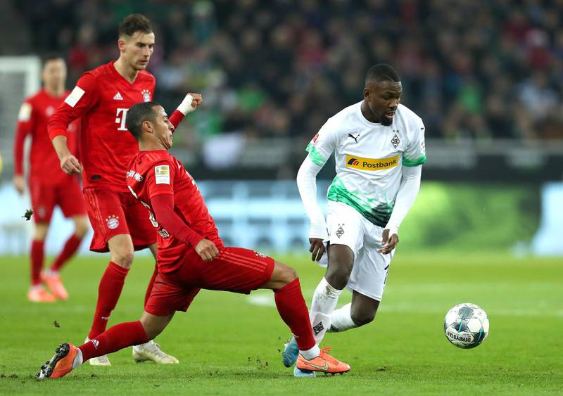 MOENCHENGLADBACH, GERMANY - DECEMBER 07: Marcus Thuram of Borussia Monchengladbach is challenged by Thiago of FC Bayern Munich during the Bundesliga match between Borussia Moenchengladbach and FC Bayern Muenchen at Borussia-Park on December 07, 2019 in Moenchengladbach, Germany. (Photo by Lars Baron/Bongarts/Getty Images)