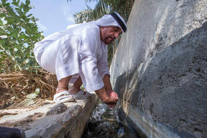 Sharjah, United Arab Emirates-  Abdullah Khilfan Al Naqbi refreshing himself on a stream of water coming from the mountain at Al Nahwa Village in Sharjah.  Leslie Pableo for The National for Ruba Haza