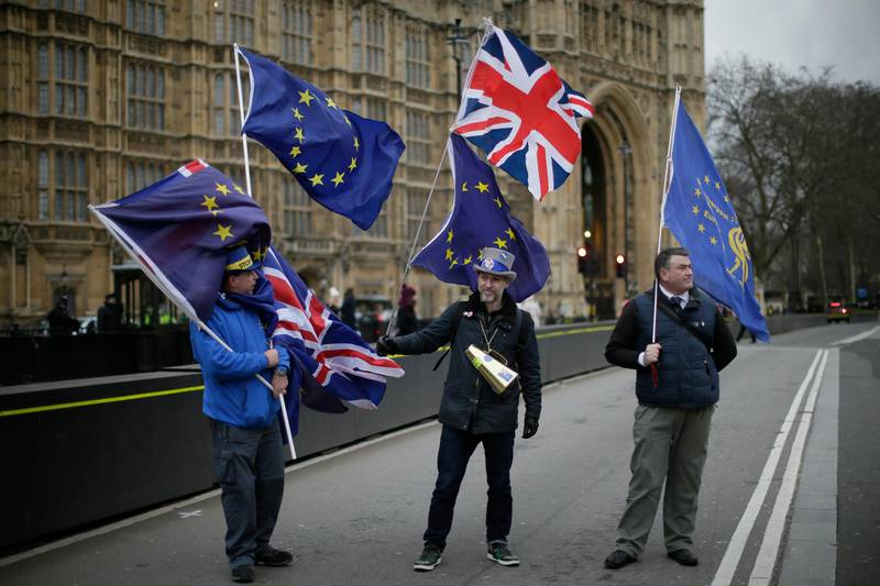 Demonstrators opposing Brexit wave flags as The European Commission's Chief Negotiator for the UK exiting the European Union, Michel Barnier is at 10 Downing Street for a meeting, outside the Houses of Parliament, London, Monday, Feb. 5, 2018. (AP Photo/Tim Ireland)