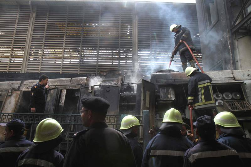 A fire fighter extinguishes flames at the scene of a fiery train crash at the Egyptian capital Cairo's main railway station on February 27, 2019. - The crash killed at least 20 people, Egyptian security and medical sources said. The accident, which sparked a major blaze at the Ramses station, also injured 40 others, the sources said. (Photo by STRINGER / AFP)
