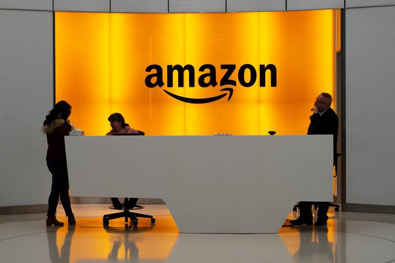 FILE - In this Feb. 14, 2019 file photo, people stand in the lobby for Amazon offices in New York.  Amazon said Friday, Jan. 31, 2020,  it now employs more than 500,000 people in the U.S., another sign of the online giant's rapid growth.  (AP Photo/Mark Lennihan, File)