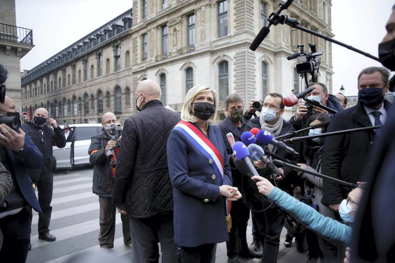 French far-right leader Marine le Pen, center, wearing a protective face mask, talks to media after laying a wreath during a ceremony Saturday, May 1, 2021 in Paris. Far-right militants usually gather at the statue for their annual May Day march. (AP Photo/Thibault Camus)