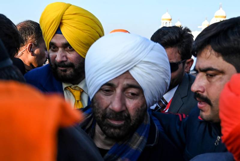 Security personnel escort Indian Bollywood actor Sunny Deol (L) and Indian politician and former cricketer Navjot Singh Sidhu (C) as they visit the Shrine of Baba Guru Nanak Dev at Gurdwara Darbar Sahib in Kartarpur, near the Indian border, on November 9, 2019. Hundreds of Indian Sikhs made a historic pilgrimage to Pakistan on November 9, crossing through a white gate to reach one of their religion's holiest sites, after a landmark deal between the two countries separated by the 1947 partition of the subcontinent. / AFP / AAMIR QURESHI