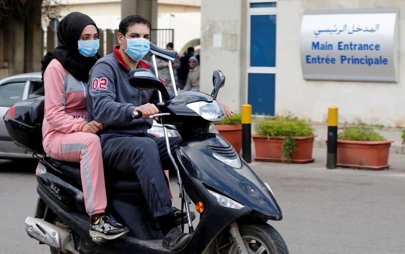 People wearing face masks ride on a motorbike outside Rafik Hariri hospital, where Lebanon's first coronavirus case is being quarantined, in Beirut, Lebanon February 21, 2020. REUTERS/Mohamed Azakir
