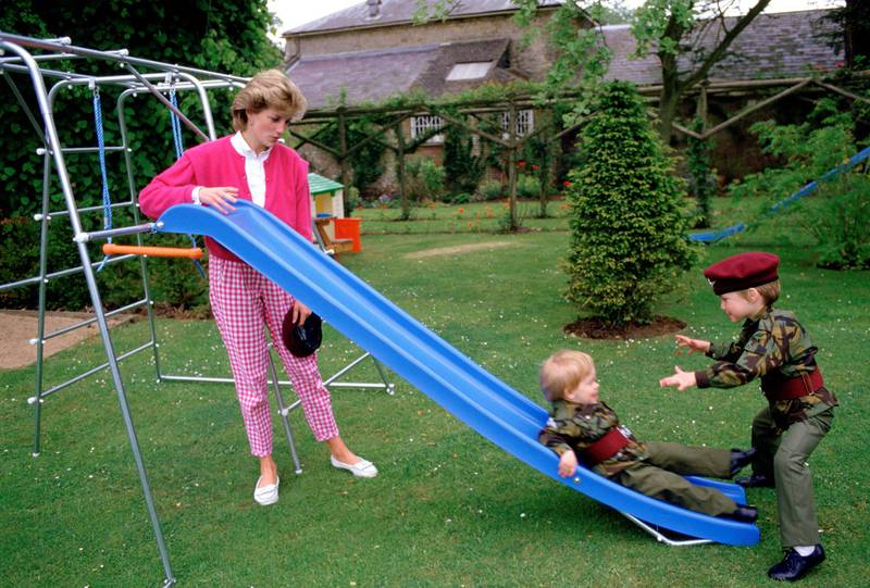 TETBURY, UNITED KINGDOM - JULY 18:  Princess Diana With Her Sons Prince William And Prince Harry Playing On A Slide In The Gardens Of Highgove House. The Boys Are Wearing The Uniforms Of The 1st Battalion Of The Parachute Regiment Of Which Their Father Is The Colonel-in-chief. Princess Diana Is Wearing A Gingham Style Pair Of Trousers.  (Photo by Tim Graham Photo Library via Getty Images)
