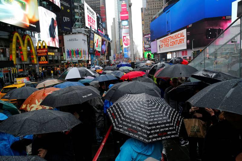 FILE PHOTO: People walk in the rain in Times Square in New York, U.S., May 13, 2017. REUTERS/Eduardo Munoz/File Photo