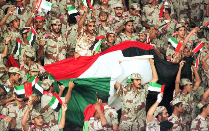 Emirati solders celebrating 10 December the victory of their team against Indonesia during an Asian Cup match in Al Ain stadium. UAE defeated Indonesia 2-0 and qualified for the quarter-finals. (Photo by RAMZI HAIDAR / AFP)