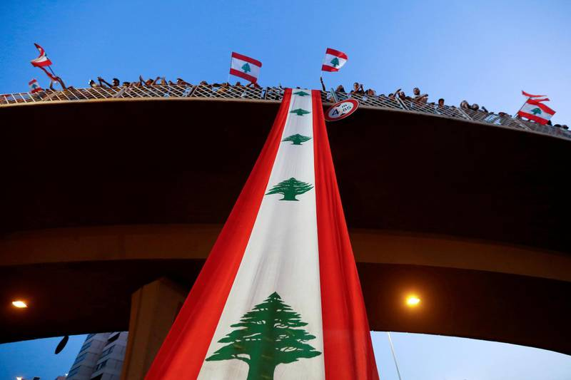 FILE PHOTO: Demonstrators stand on a bridge decorated with a national flag during an anti-government protest along a highway in Jal el-Dib, Lebanon October 21, 2019. REUTERS/Mohamed Azakir/File Photo