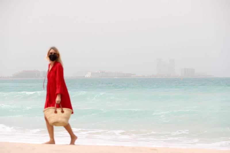 Dubai, United Arab Emirates - Reporter: N/A. News. Weather. A lady walks on the beach on a hazy sandy day in Dubai. Sunday, March 14th, 2021. Dubai. Chris Whiteoak / The National