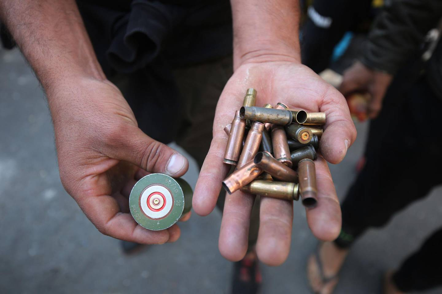 Iraqi anti-government protesters display spent bullet casings during clashes with security forces in al-Rasheed street near al-Ahrar bridge on November 22, 2019. Three anti-government protesters were killed in Iraq's capital, a medical source said, in clashes between defiant demonstrators and security forces trying to keep them back from state offices.  More than 340 people have died and thousands have been wounded since rallies against widespread graft and unemployment erupted in Baghdad and the mostly-Shiite south last month.  / AFP / AHMAD AL-RUBAYE