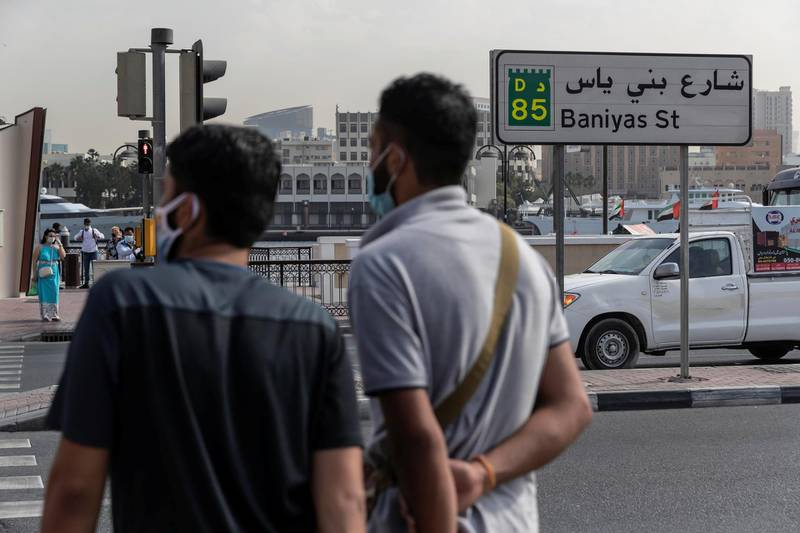 DUBAI, UNITED ARAB EMIRATES. 25 FEBRUARY 2021. COVID - 19 Standalone. Deira souk during the time of Covid. Two mean wait to cross Baniyas str while wearing masks. The are was previously under police lockdown due to it's high cases of covid-19. (Photo: Antonie Robertson/The National) Journalist: Nick Webster. Section: National.