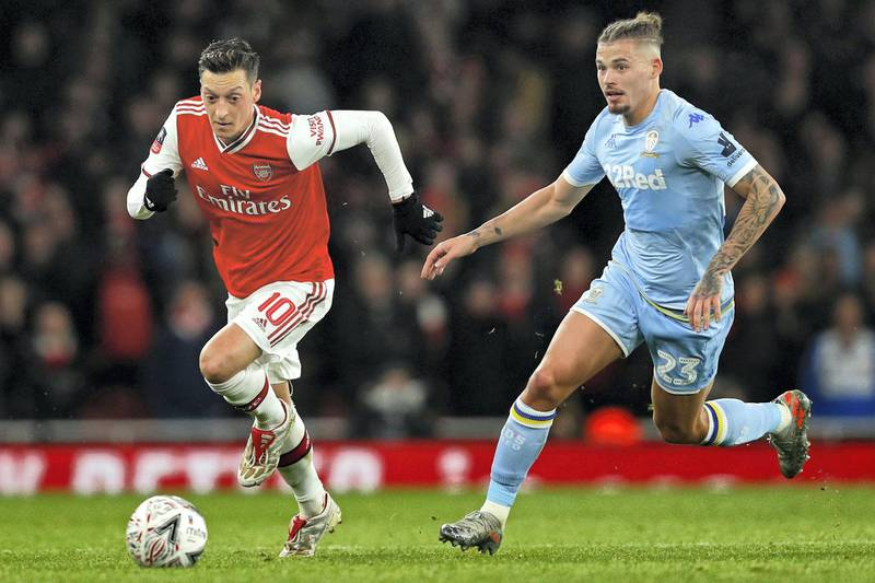 Arsenal's German midfielder Mesut Ozil (L) runs away from Leeds United's English midfielder Kalvin Phillips (R) during the English FA Cup third round football match between Arsenal and Leeds United at The Emirates Stadium in London on January 6, 2020. (Photo by Adrian DENNIS / AFP) / RESTRICTED TO EDITORIAL USE. No use with unauthorized audio, video, data, fixture lists, club/league logos or 'live' services. Online in-match use limited to 120 images. An additional 40 images may be used in extra time. No video emulation. Social media in-match use limited to 120 images. An additional 40 images may be used in extra time. No use in betting publications, games or single club/league/player publications. /