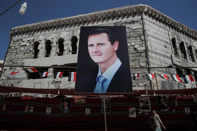 FILE PHOTO: A man walks past a banner depicting Syrian president Bashar al-Assad in Douma, outside Damascus, Syria, September 17, 2018. REUTERS/Marko Djurica/File Photo