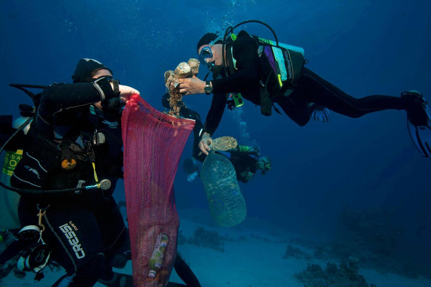 In this June 8, 2018 photo, divers collect plastic and other debris during a cleanup organized by Camel Dive Club, at a dive site off the coast of the Red Sea resort of Sharm el Sheik, in Southern Sinai, Egypt. An Egyptian official says his Red Sea province will impose a ban on disposable plastics, prohibiting everything from single use straws to plastic bags in an effort to fight plastic pollution. Ahmed Abdallah, governor of Hurghada province, said late on Tuesday, April, 2, 2019, that the ban will go into effect from June. (AP Photo/Thomas Hartwell,)