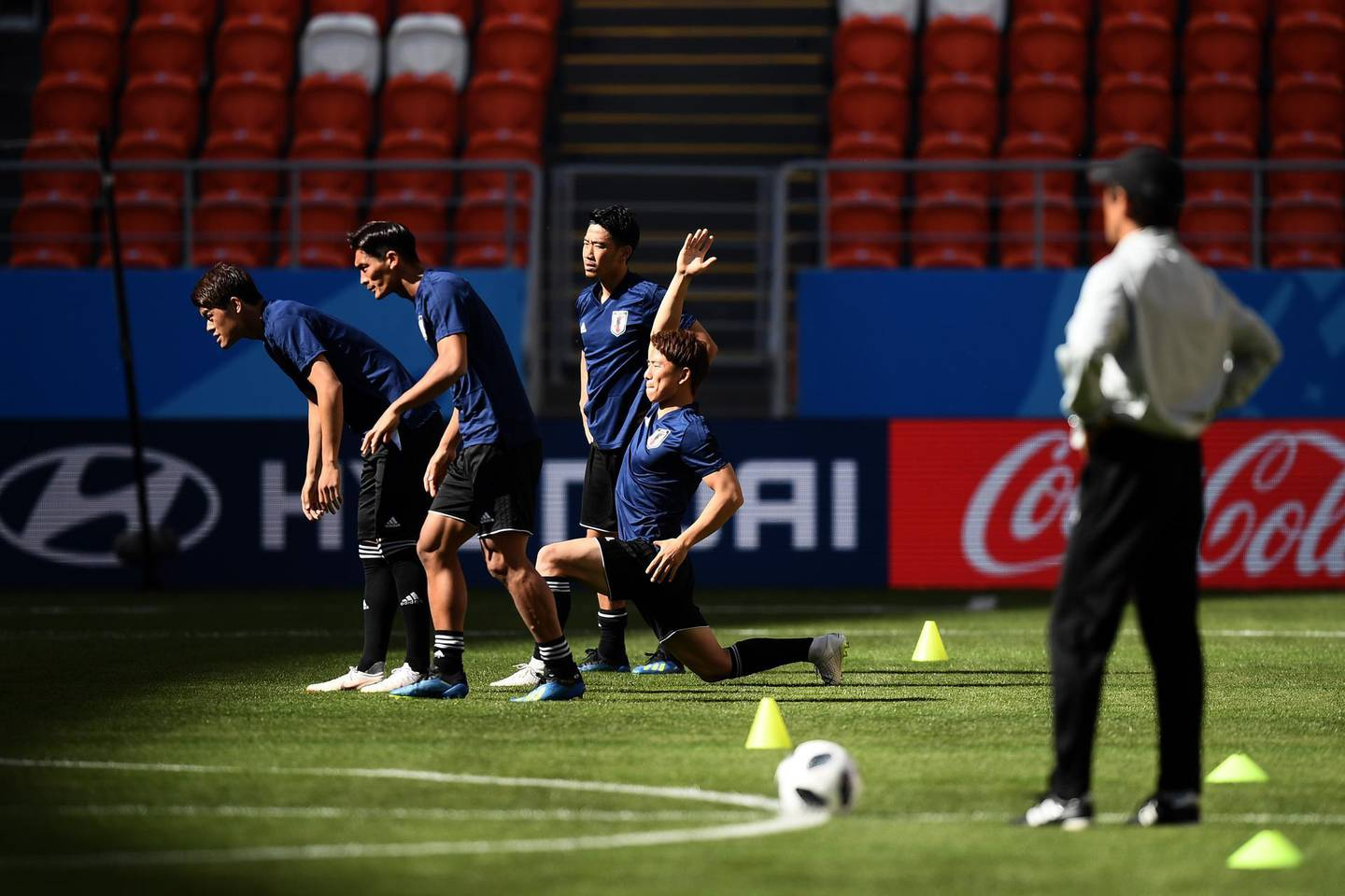 SARANSK, RUSSIA - JUNE 18: Japan's manager Akira Nishino (R) looks on as players stretch during a training session ahead of the FIFA World Cup Group H match between Colombia and Japan at Mordovia Arena on June 18, 2018 in Saransk, Russia. (Photo by Carl Court/Getty Images)