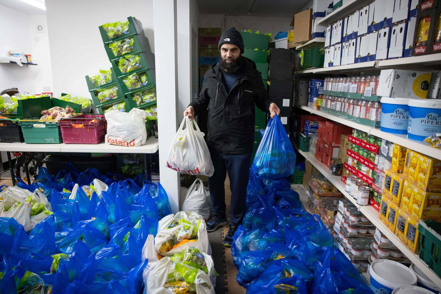 """Elyas Ismail, founder of the Newham Community Project food bank, organises food packages ahead of their collection by international students, in east London on February 16, 2021. """"It's hard to buy food, the prices are so much higher than in India"""": without work or state aid, young foreign students, like Jay Patel, came to the United Kingdom to realise their dreams are plunged into poverty because of the pandemic. Despite the rain, dozens of young people like him, hoods on their heads and shopping bags in their hands, congregate in front of the small room of the Newham Community Project association, in East London, to collect rice, vegetables and other foodstuffs. The Newham Community Project, in partnership with Abdullah Aid, provides a weekly food bank service where food and essentials are provided to over 1000 students every week. / AFP / TOLGA AKMEN / TO GO WITH AFP STORY by Charlotte DURAND"""