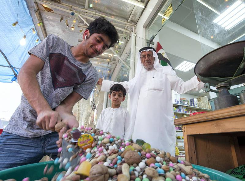 RAS AL KHAIMAH, UNITED ARAB EMIRATES, 26 APRIL 2018- Abdulla Ali Mohsin owner of Islamic Trading Est.,  one of the stores selling sweets and nuts for Hag Al Leila with his grandsons in Ras Al khaimah. Leslie Pableo for The National for Anna Zackarias story