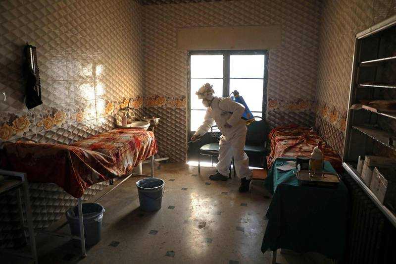 """A member of the Syrian Civil Defence known as the """"White Helmets"""" disinfects a hospital room, as part of preventive measures taken against infections by the novel coronavirus, in the Syrian town of Dana, east of the Turkish-Syrian border in the northwestern Idlib province, on March 22, 2020.  Unlike Syria, its five neighbours, Iraq, Israel, Jordan, Lebanon and Turkey, have all reported cases of coronavirus. The rebel-held and densely-populated province of Idlib in northwest Syria, besieged by government forces and facing severe shortages of medical supplies and facilities, would suffer the most from an outbreak.  / AFP / AAREF WATAD"""