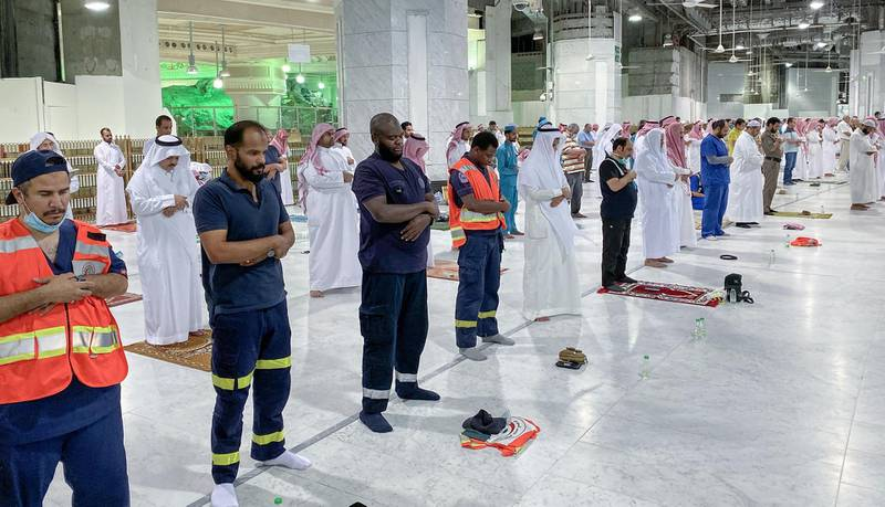 """Muslim worshippers perform the """"Tarawih"""" nightly prayer during the holy month of Ramadan, while keeping their distance amid the COVID-19 pandemic, at the Grand Mosque, Islam's holiest site, in the Saudi city of Mecca, late on May 8, 2020. - Saudi Authorities allowed for a limited number of worshippers to enter the Grand Mosque to perform prayers during Ramadan, amid unprecedented bans on family gatherings and mass prayers due to the novel coronavirus (COVID-19) pandemic. (Photo by STR / AFP)"""