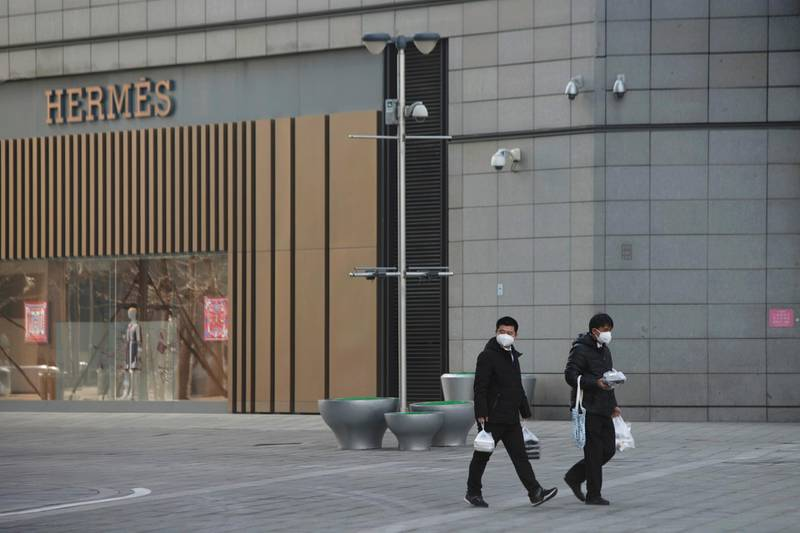 Men wearing face masks walk with takeaway food past a Hermes store at a shopping centre after the extended Lunar New Year holiday caused by the novel coronavirus outbreak, in Beijing's central business district, China February 10, 2020. REUTERS/Stringer   NO RESALES. NO ARCHIVES.
