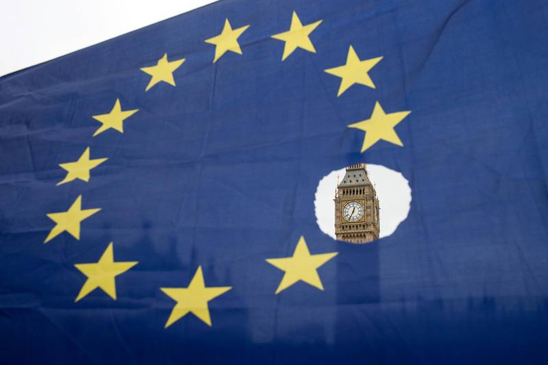 (FILES) In this file photo taken on March 29, 2017 a pro-remain protester holds up an EU flag with one of the stars symbolically cut out, in front of the Houses of Parliament shortly after British Prime Minister Theresa May announced to the House of Commons that Article 50 had been triggered in London.  A bill enacting Britain's decision to leave the European Union has become law after months of debate, the speaker of parliament announced on June 26, 2018, to cheers from Conservative Party lawmakers. / AFP / OLI SCARFF