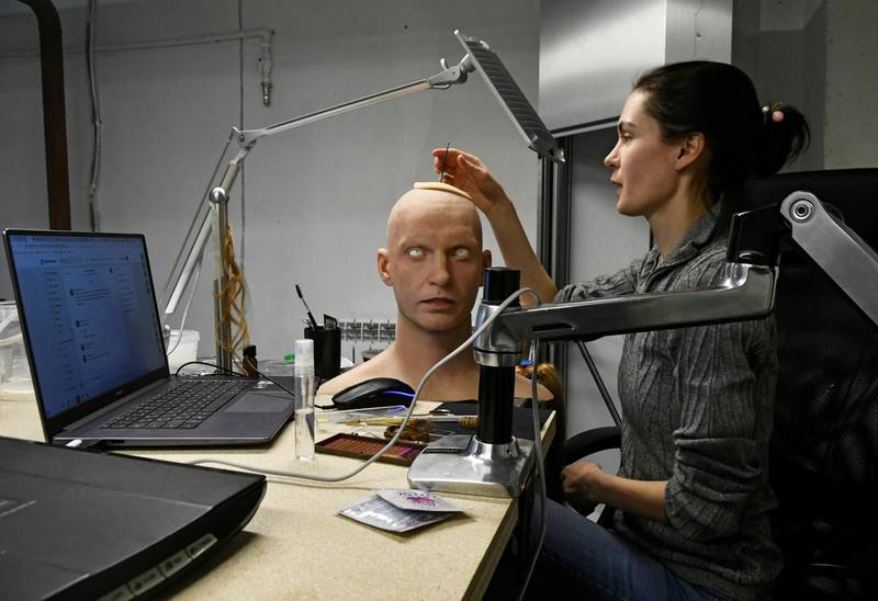 Alexandra Chegodaeva, an assistant chief of Promobot research and development department, works on a head of a humanoid robot at the company's branch in the far eastern city of Vladivostok, Russia March 15, 2021. REUTERS/Yuri Maltsev