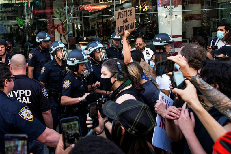 FILE PHOTO: Demonstrators scuffle with NYPD police officers as they try to march trough Times Square during a protest against racial inequality in the aftermath of the death in Minneapolis police custody of George Floyd, in New York City, New York, U.S. June 14, 2020. REUTERS/Eduardo Munoz/File Photo